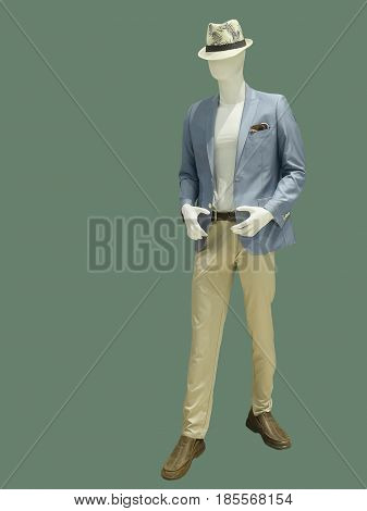 Full length male mannequin dressed in suit and hat over green background. No brand names or copyright objects.