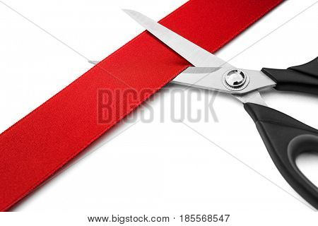Red Ribbon Cutting Ceremony -Scissors cutting red ribbon or tape against white background