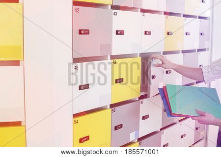 Cropped image of businessman putting files in locker at creative office