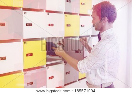 Side view of creative businessman putting files in locker at office