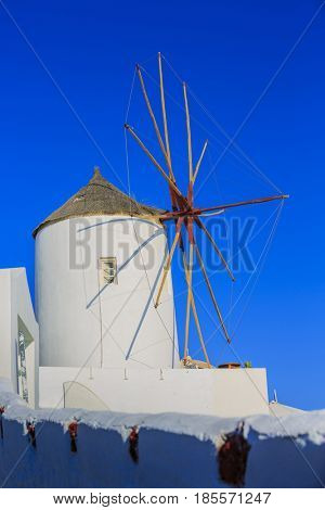 Picturesque view of Old Town Oia on the island Santorini, white houses, windmills and church with blue domes, Greece