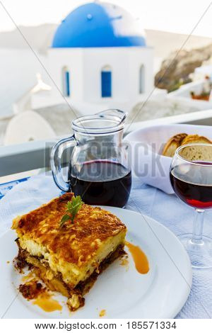 Greek moussaka with eggplants, ground beef and potatoes. Picturesque view of Old Town of Oia on the island Santorini.