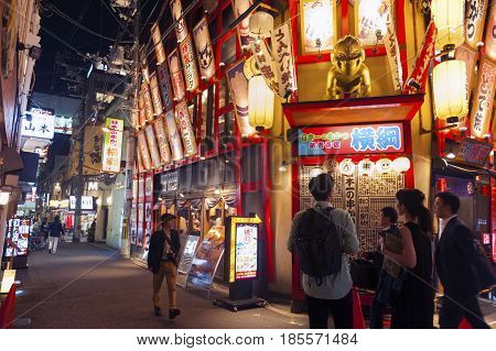 Osaka, Japan - April 2016: Nightlife On Street Of Osaka City Along With Shops, Bars, And Restaurants