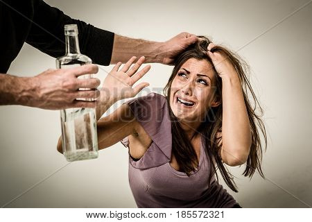Angry aggressive drunk husband is physically abusing his wife.