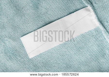 Blank white clothes label on blue knitted cloth
