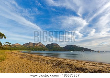 People walking on Freycinet national park beach in the evening, Hazards mountain range can be seen from Coles Bay in East coast of Tasmania, Australia