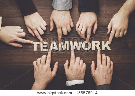 Teamwork concept. Different hands of men and women connect letters into word teamwork. Teamwork concept on the brown table. Each has its own role in team. Word teamwork out of wooden letters.