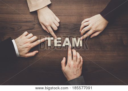 Team concept. Different hands of men and women connect letters into word team. Team concept on the brown wooden table background. Each has its own role in team.