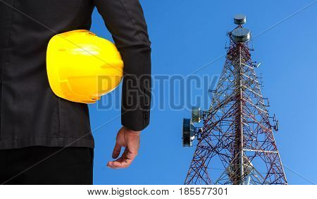 back view of businessman in suite with yellow safety helmet with telecommunication tower with blue sky background technology business and industrial concept.