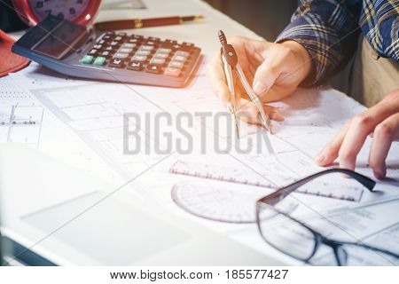 Architect Or Engineer Working In Office On Blueprint. Architects Workplace , Blueprints, Ruler, Helm