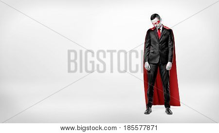 A sad businessman in a superhero red cape standing on white background with his shoulders slumped. Business and risk. Failure and doubt. Unexpected trouble.