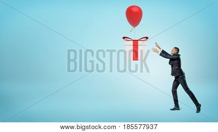 A small businessman trying to catch a big gift box that is flying away on a balloon. Gifts and presents. Sales and promotions. Business aspirations.