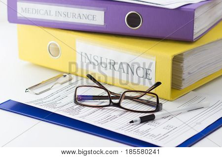 Clean Insurance Form On The Clipboard, Folders, Glasses And Pen
