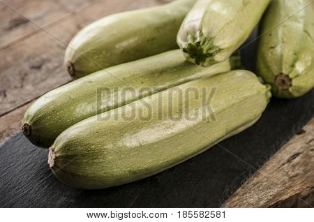 Fresh zucchini on wooden background close up