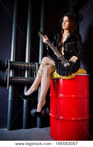 Portrait Of Sexy Nude Brunette Girl At Black Leather Jacket With Guitar Against Industrial Backgroun