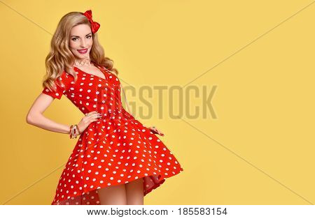 Fashion Woman Smiling in Red Polka Dots Summer Dress. PinUp Sensual Blond Girl Having fun. Trendy Stylish Curly hairstyle, Makeup, red Bow. Glamour Playful Sexy Beauty pinup Model. Vintage on Yellow