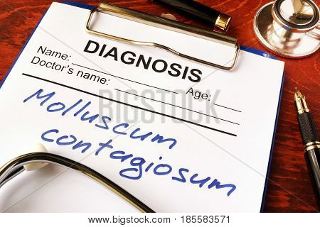 Molluscum contagiosum (MC) written in a document on a table.