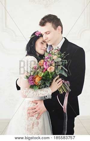 Beautiful Bride and Groom Hugging. Fashion Model Woman and Handsome Man in Love. Wedding Couple