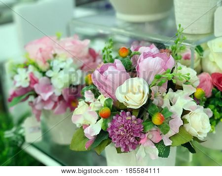 Decoration of white pink and purple synthetic flower in white vase