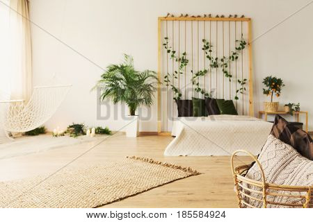Monochromatic beige bedroom with bed blanket basket and rug