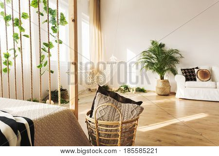 Multifunctional apartment with bed couch plant and rope wall