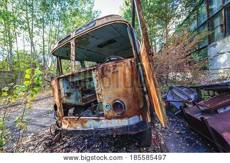 Bus wreck in desolate factory in Pripyat desolate city in Chernobyl Exclusion Zone Ukraine