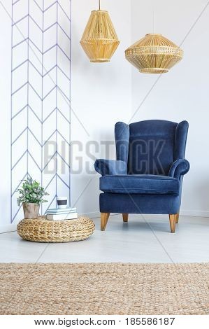 White room with decorative wall tape blue armchair lamp pouf