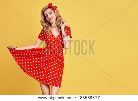 Fashion Beauty. PinUp Sensual Blond Girl Smiling in Red Polka Dots Summer Dress. Woman in fashion pose. Trendy Stylish Curly hairstyle, fashion Makeup, red Bow. Glamour Playful Sexy pinup Model Lady