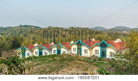 Multi colored row houses on top of a hill station with mountain in the background,Salem, Yercaud, tamilnadu, India, April 29 2017