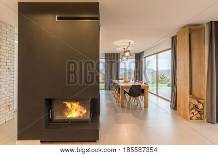 Modern fireplace and wooden table in spacious house