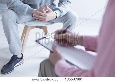 Psychologist taking notes during meeting with his teenage patient