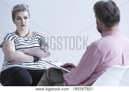 Troubled girl with tattoo and dark makeup talking with psychologist