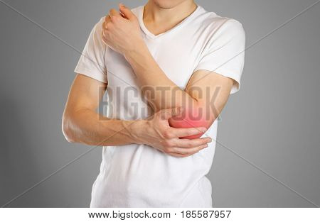 A Man Holds The Elbow. The Pain In My Arm. A Sore Point In Red. Closeup. Isolated