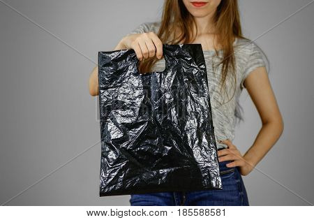 Girl Holds A Black Plastic Bag. Closeup. Isolated