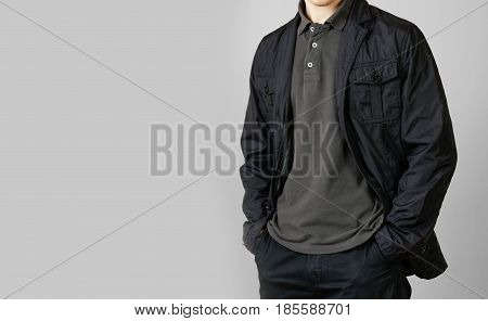 A Man In A Black Jacket. Hands In His Pockets. Isolated On Grey Background