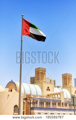 United Arab Emirates flag against blue sky in Sharjah selective focus United Arab Emirates.