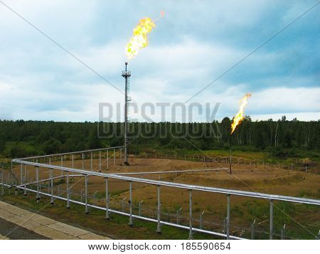 Picture of two gas flares burning and smoking