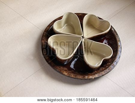 Four ceramic bowls in the shape of heart on round ceramic plate