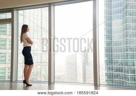 Young woman standing near skyscraper window and looking on urban landscape. Businesswoman thinking about plans on future while contemplating the cityscape. Inspiration in business concept. Copy space