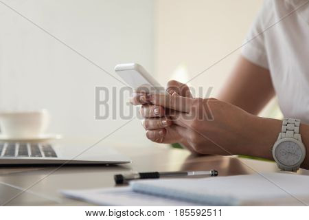 Close up image of modern cellphone in womans hand at desk with laptop. Office worker boring at workplace and playing games, writing in social networks. Businesswoman looking important contact on phone