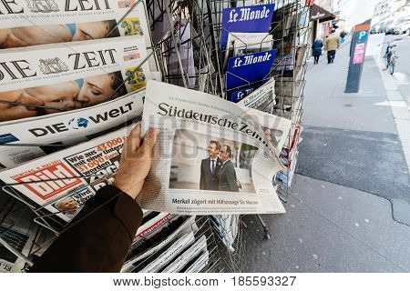 PARIS FRANCE - MAY 9 2017: Pov buying suddeutsche zeitung newspaper front page with the picture of the newly elected French president Emmanuel Macron after the second round French Presidential election