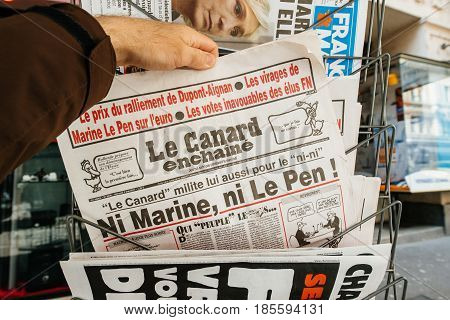 PARIS FRANCE - MAY 9 2017: Pov buying le canard enchaine newspaper front page with NINI phrase Ni Marine Ni le Pen
