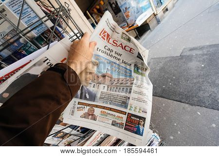 PARIS FRANCE - MAY 9 2017: Pov buying L'Alsace newspaper front page with the picture of the newly elected French president Emmanuel Macron after the second round French Presidential election