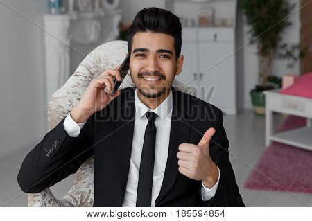 Young Handsome Businessman Talking On Mobile Phone And Shows Thumb Up Sign.