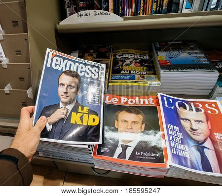 PARIS FRANCE - MAY 9 2017: Pov buying magazines L`Express and Le Point with front page of the newly elected French president Emmanuel Macron second round French Presidential election