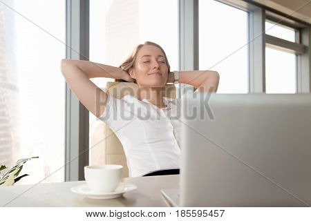 Businesswoman takes minute break for coffee and leaning back in chair with hands behind head. Successful female entrepreneur relaxing with satisfaction at workplace. Pleasure from great job done
