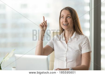 Surprised woman sitting at desk in front of laptop with raised forefinger. Female entrepreneur found life hack unexpected problem solution, has great idea. Businesswoman remembered something important