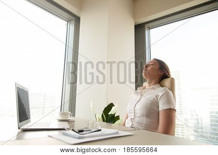 Businesswoman has deep relaxation at workplace. Relaxed woman sitting with closed eyes at the desk with laptop in office. Short recovering sleep on work. Minute break for increasing productivity