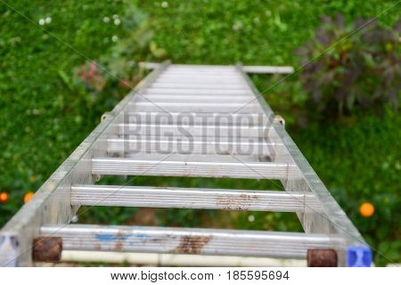 Top View Of A Long Silver Aluminum Ladder Leaning Against The Wall Of The House. Close Up View From