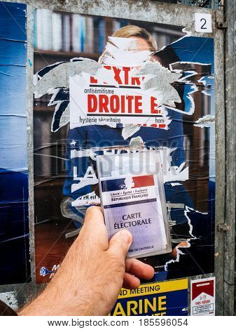 PARIS FRANCE - MAY 9 2017: Carte Electorale in front of Marine Le Pen portrait poster detail next to polling place after the second round of the French presidential election